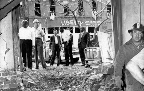 In this Sept. 15, 1963 file photo, emergency workers and others stand around a large crater from a bomb which killed four black girls in the Sixteenth Street Baptist Church in Birmingham, Ala. The windows of the building across the street in the background were also blown out. (AP Photo)